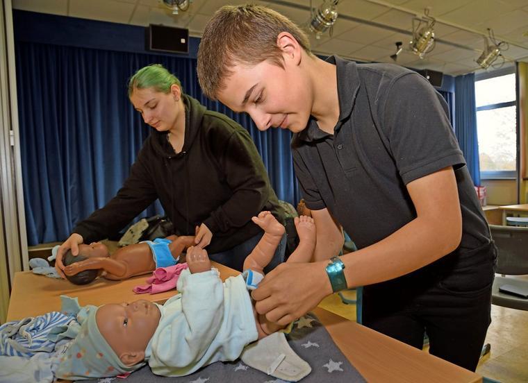 Jorden und Sina wickeln ihre Baby-Simulatoren namens Tempelton und Iva mit frischen Windeln
