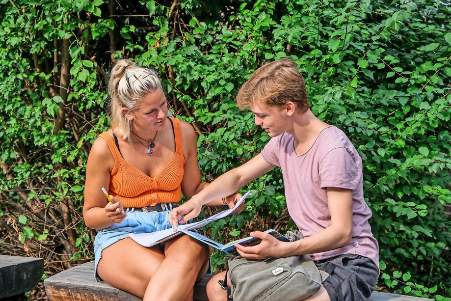 Berit und Johann sitzen draußen auf einer Bank und lernen gemeinsam.